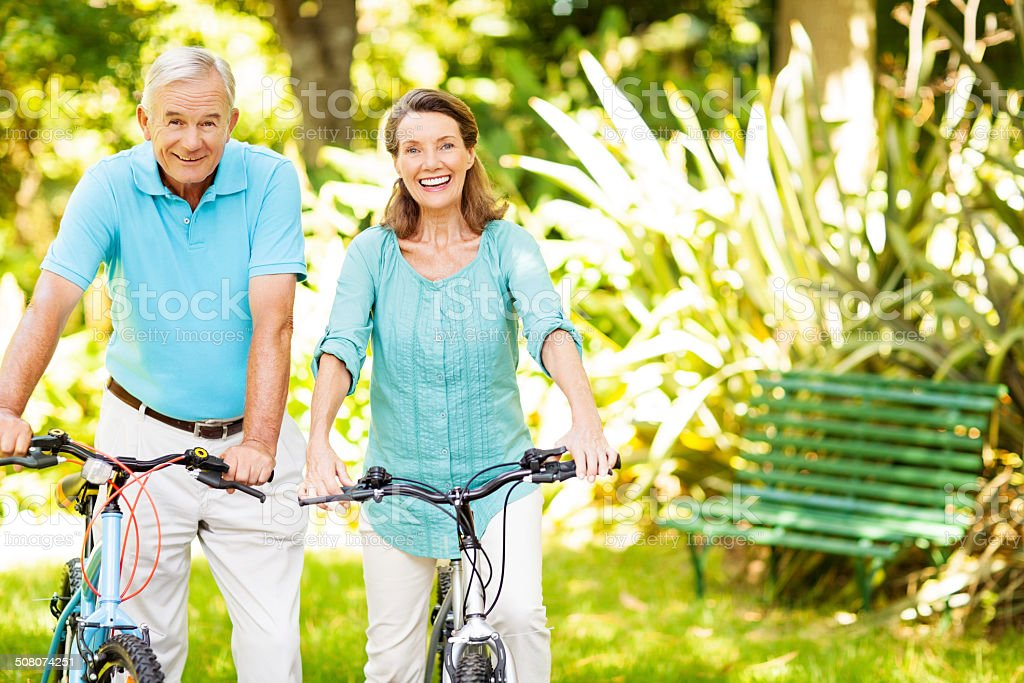Senior Couple Holding Bicycles In Park royalty-free stock photo