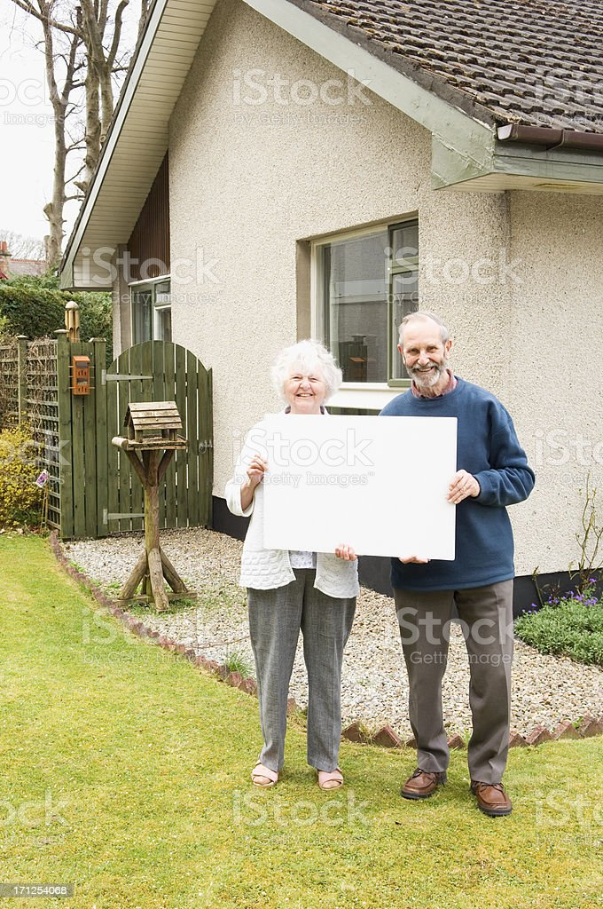 Senior couple holding blank sign royalty-free stock photo