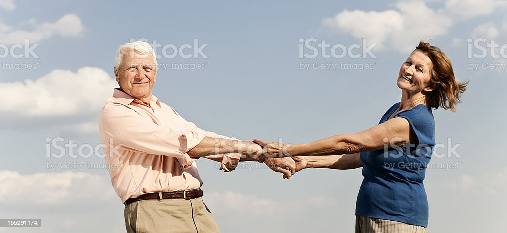 A senior couple holding each other on a sunny day royalty-free stock photo
