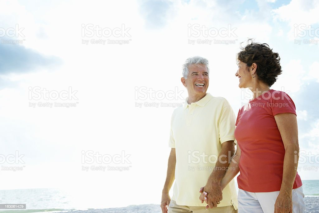 Senior couple holding hands and walking on a beach royalty-free stock photo
