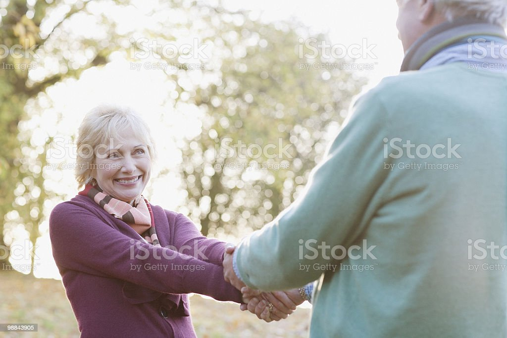 Senior couple holding hands in park stock photo