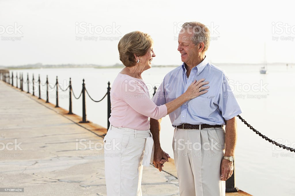 Senior couple holding hands, laughing stock photo