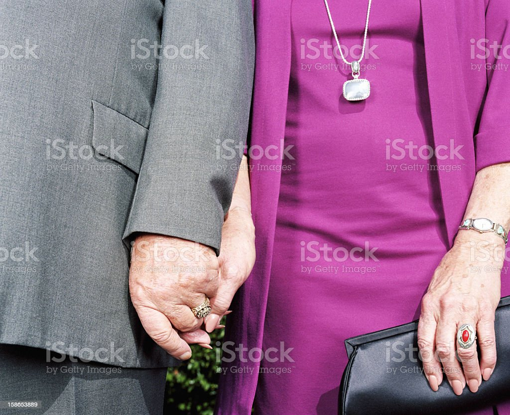 Senior couple holding hands, mid section stock photo