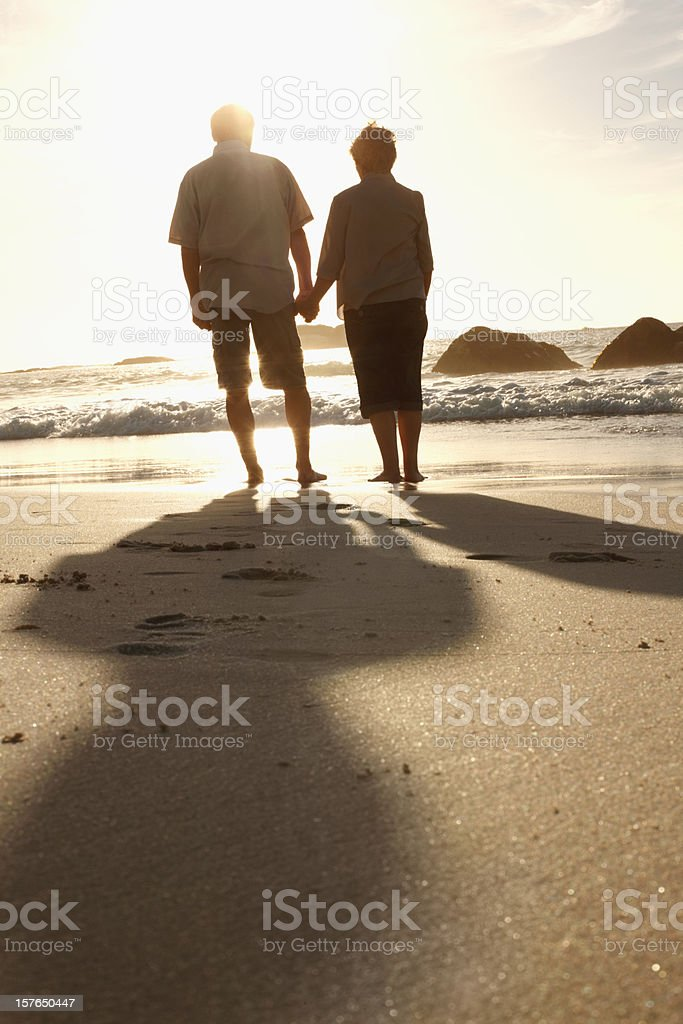 Senior couple holding hands on the beach at sunset royalty-free stock photo
