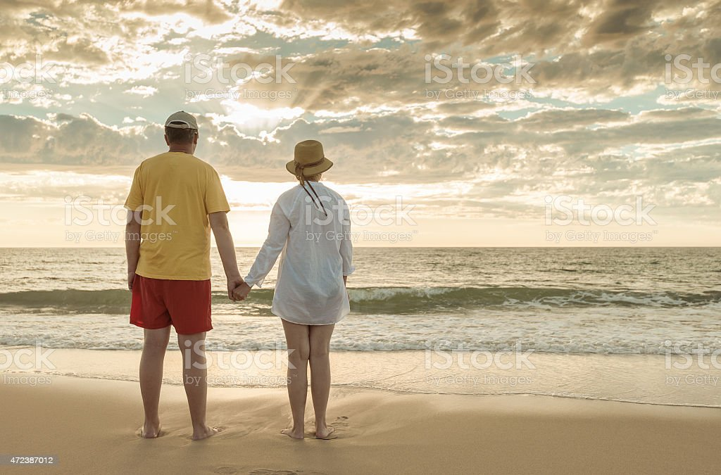 Senior couple holding hands on the beach stock photo