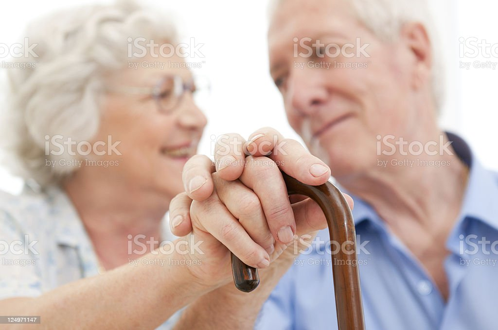 A senior couple holding hands on top of a cane handle stock photo