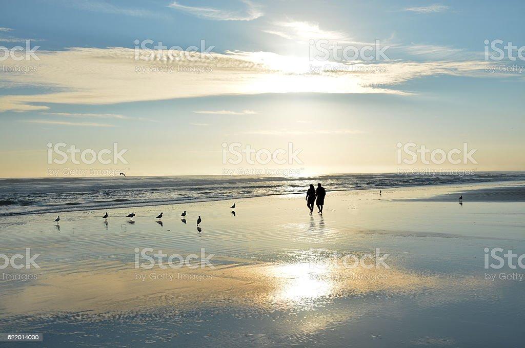 Senior couple holding hands walking on beach enjoying sunrise. stock photo