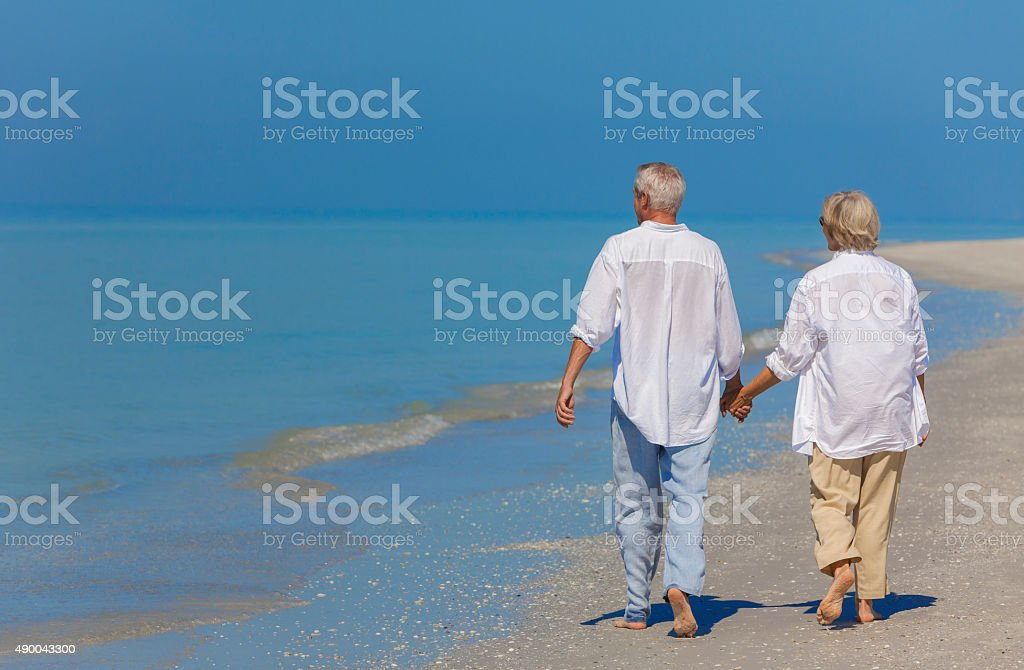 Senior Couple Holding Hands Walking on Beach stock photo
