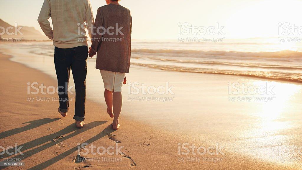 Senior couple holding hands walking on the beach stock photo