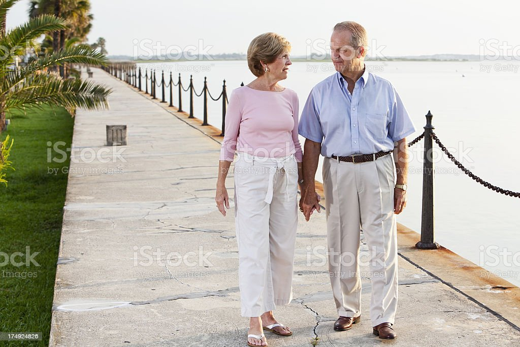 Senior couple holding hands, walking stock photo