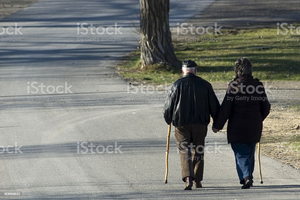 A senior couple holding hands while taking a stroll together stock photo