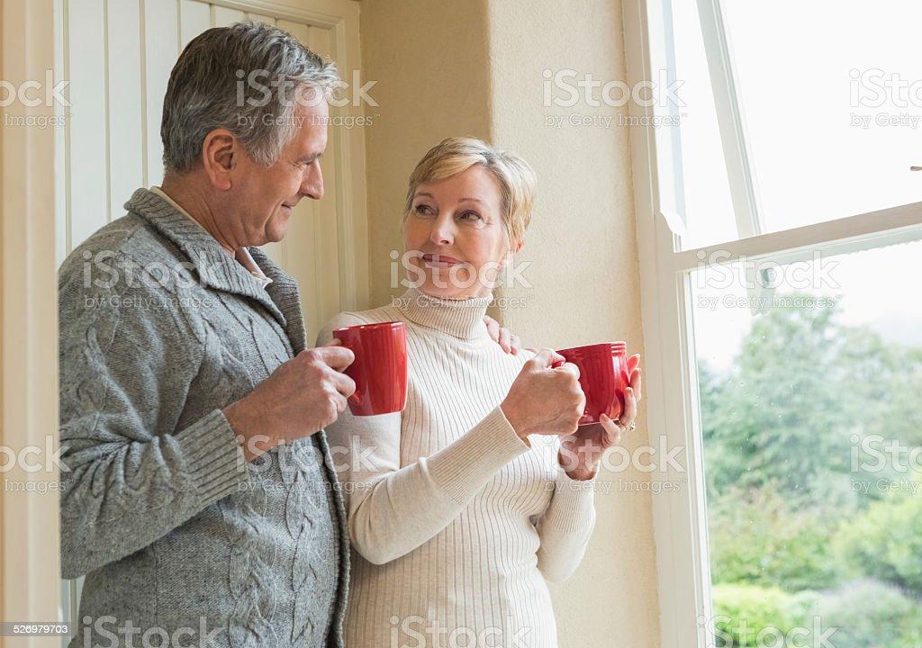 Senior couple holding red mugs stock photo