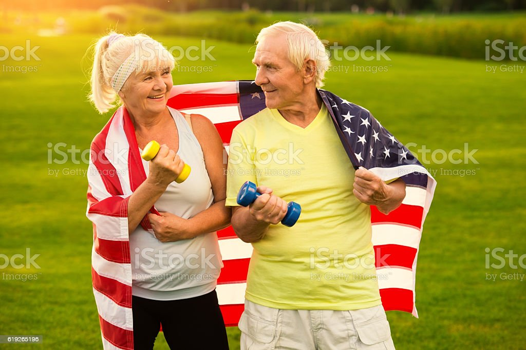 Senior couple holds dumbbells. stock photo