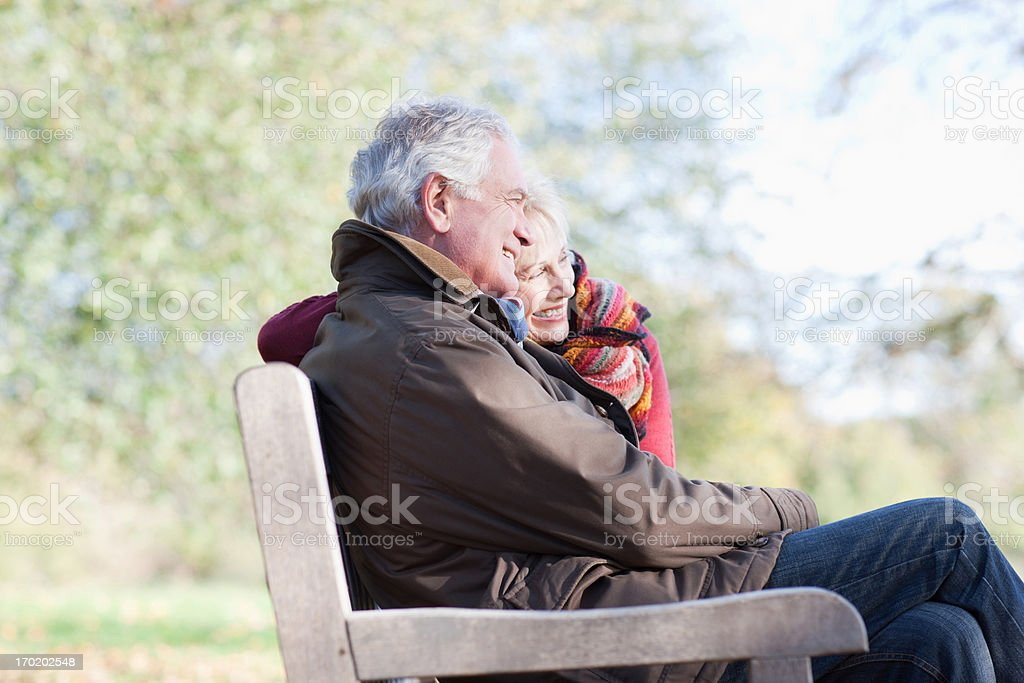 Senior couple hugging in park bench stock photo