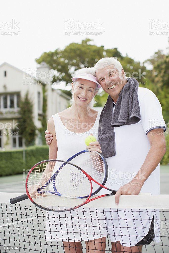 Senior couple hugging on tennis court stock photo