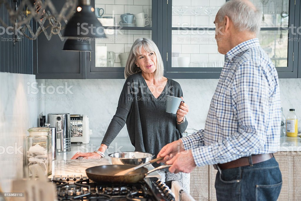 Senior couple in a kitchen making dinner and talking stock photo