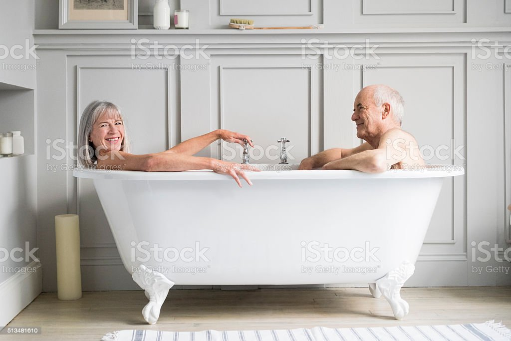 Senior couple in bath together smiling stock photo