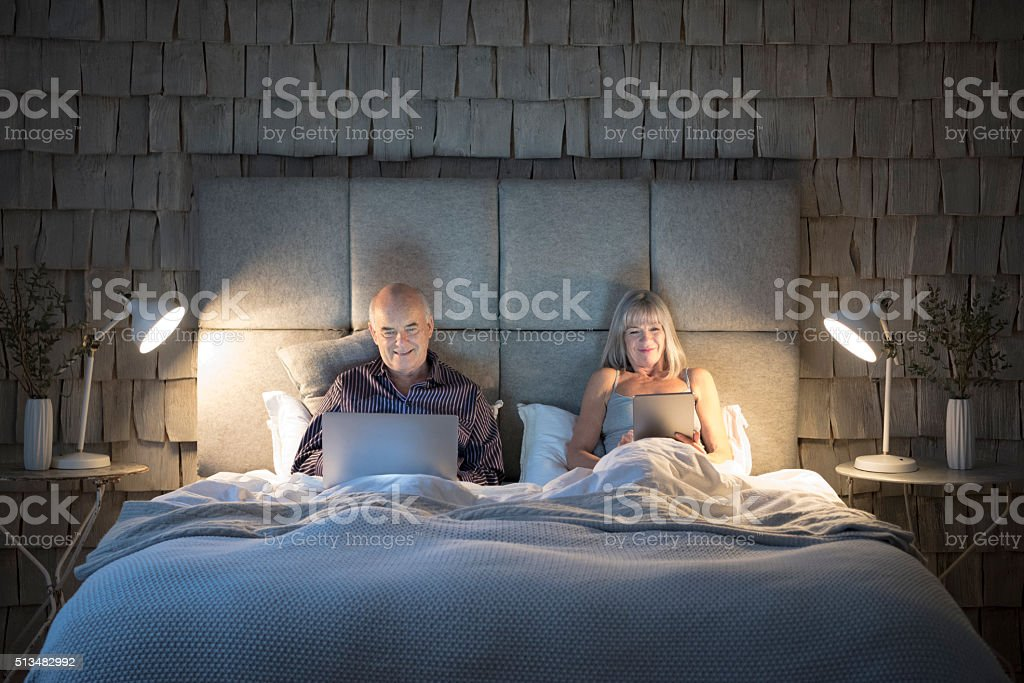 Senior couple in bed at night with laptop and tablet stock photo