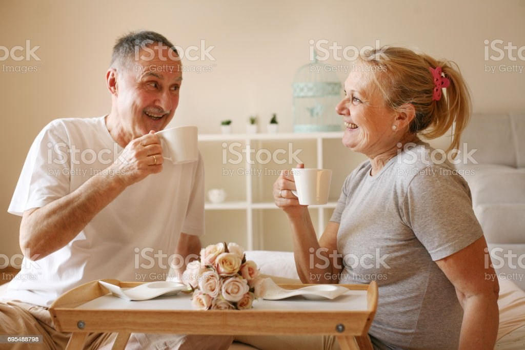 Senior couple in bed. Senior people drinking coffee in bed. stock photo