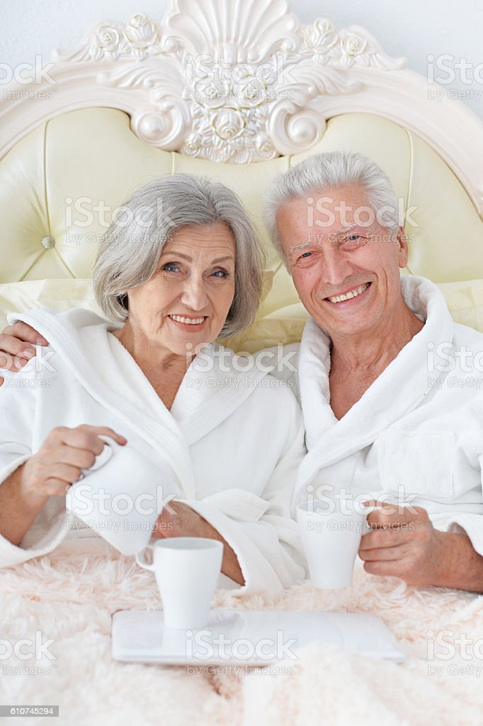 Senior couple  in bed  with coffee stock photo