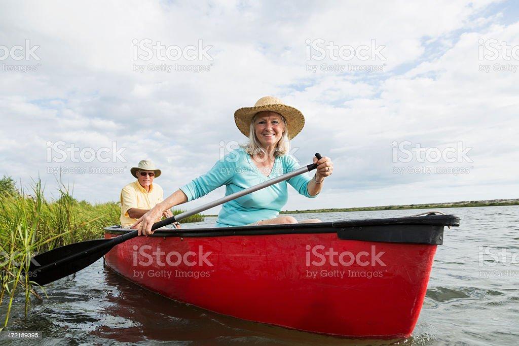 Senior couple in canoe on water stock photo