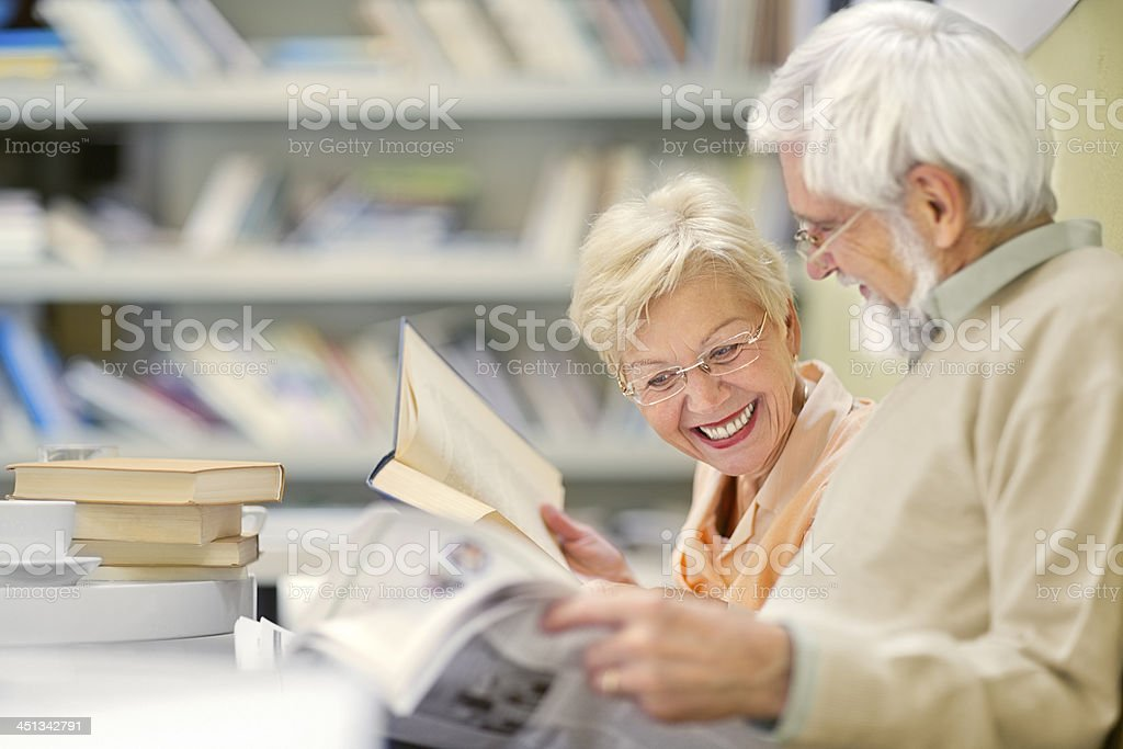 Senior couple in coffee shop have fun and reading stock photo