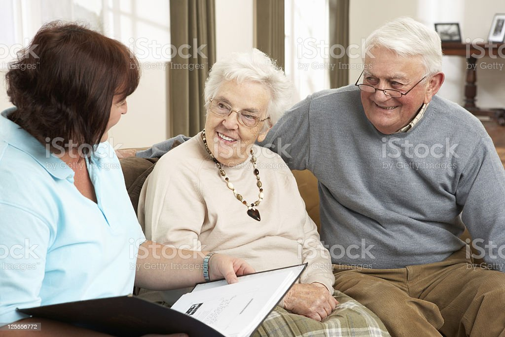 Senior Couple In Discussion With Health Visitor At Home royalty-free stock photo