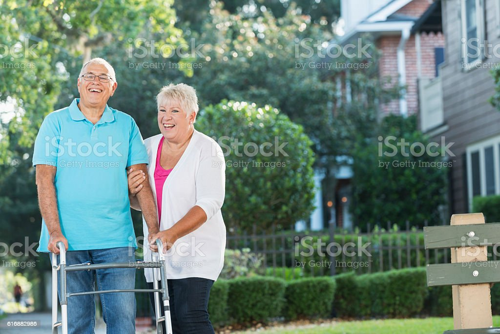 Senior couple in front of house, man using walker stock photo