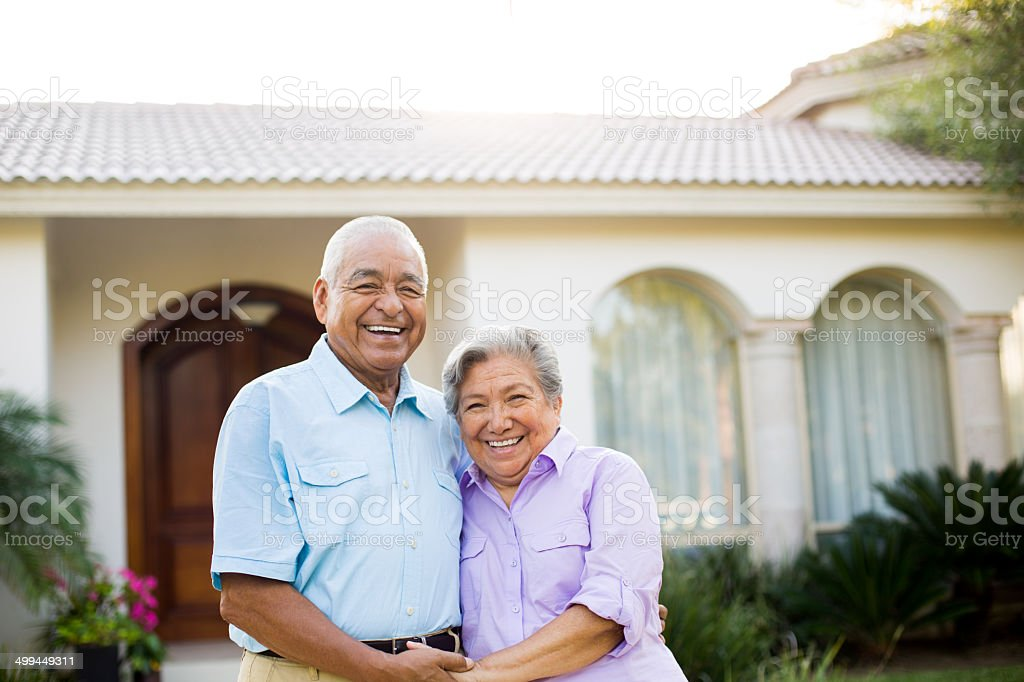 Senior couple in front of house stock photo