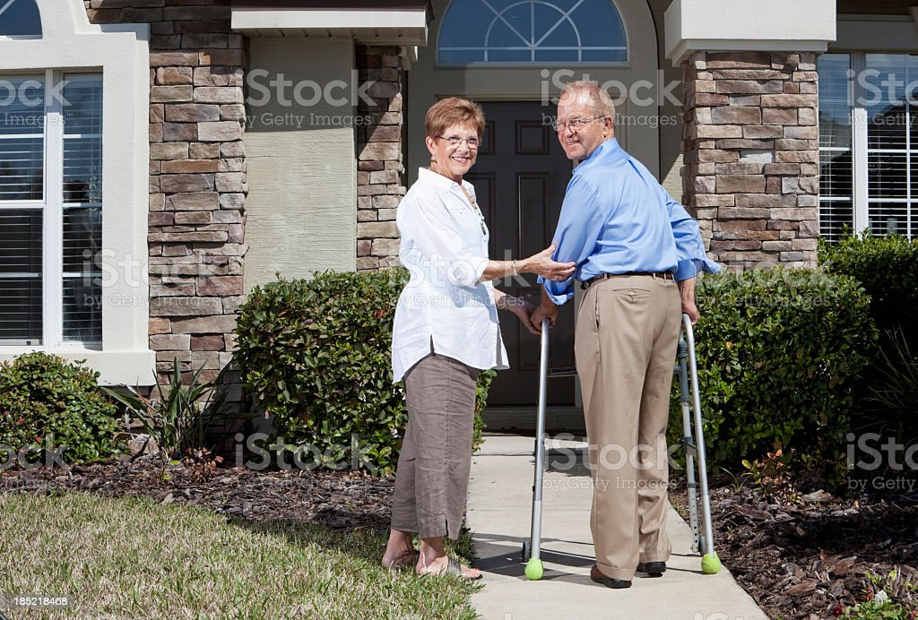 Senior couple in front of house, using walker royalty-free stock photo