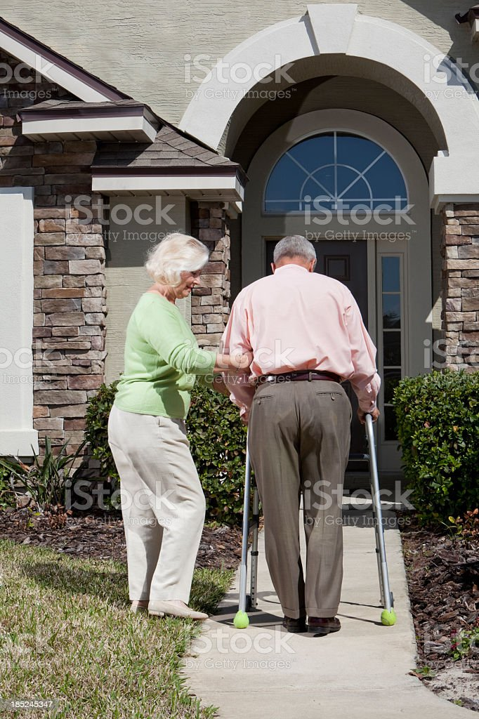 Senior couple in front of house, using walker stock photo