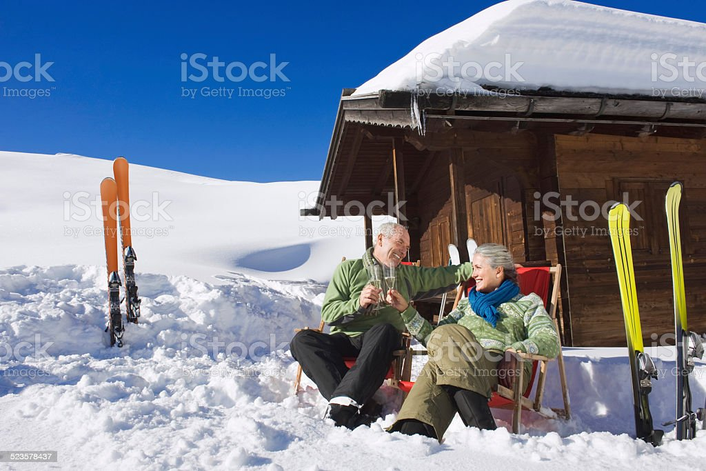 Senior couple in front of log cabin, holding champagne glasses stock photo
