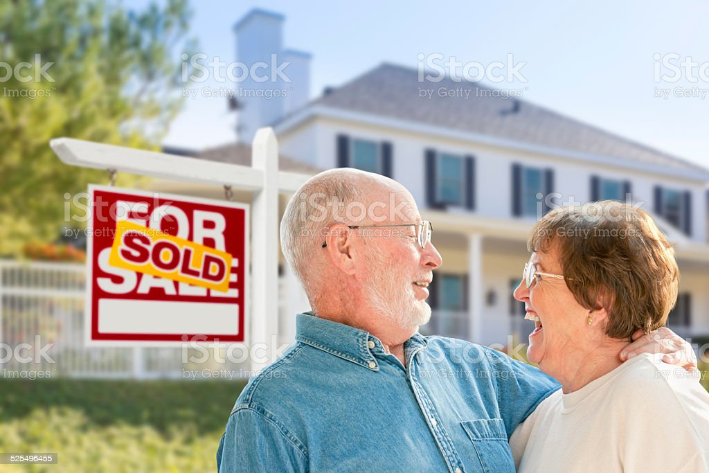 Senior Couple in Front of Sold Real Estate Sign, House stock photo
