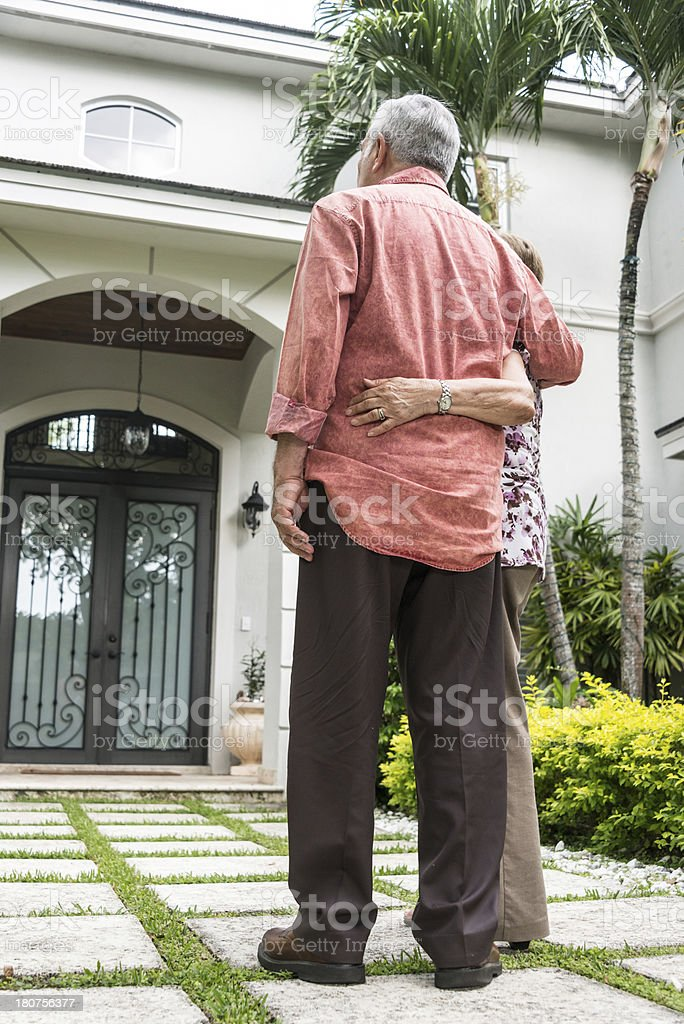 Senior couple in front of their house stock photo