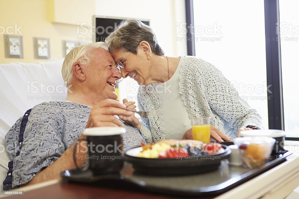 Senior Couple In Hospital Room As Male Patient Has Lunch stock photo