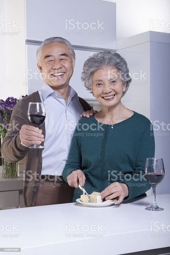 Senior Couple in Kitchen Drinking Wine and Cheese royalty-free stock photo