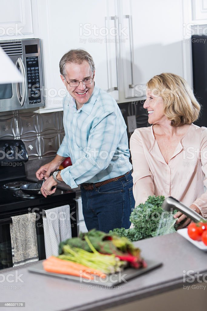 Senior couple in kitchen preparing dinner together stock photo