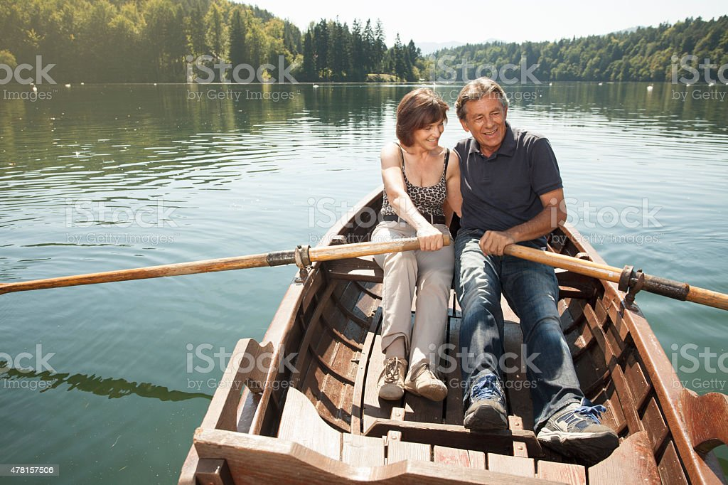 Senior couple in love in a boat on a lake stock photo