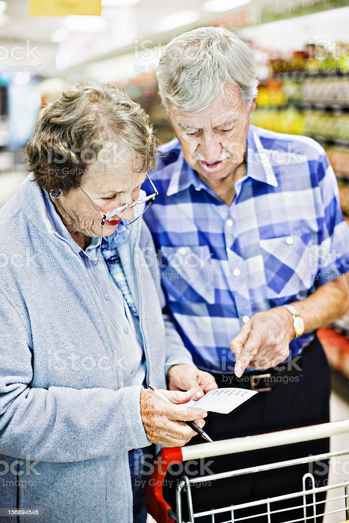 Senior couple in supermarket look at shopping list together stock photo