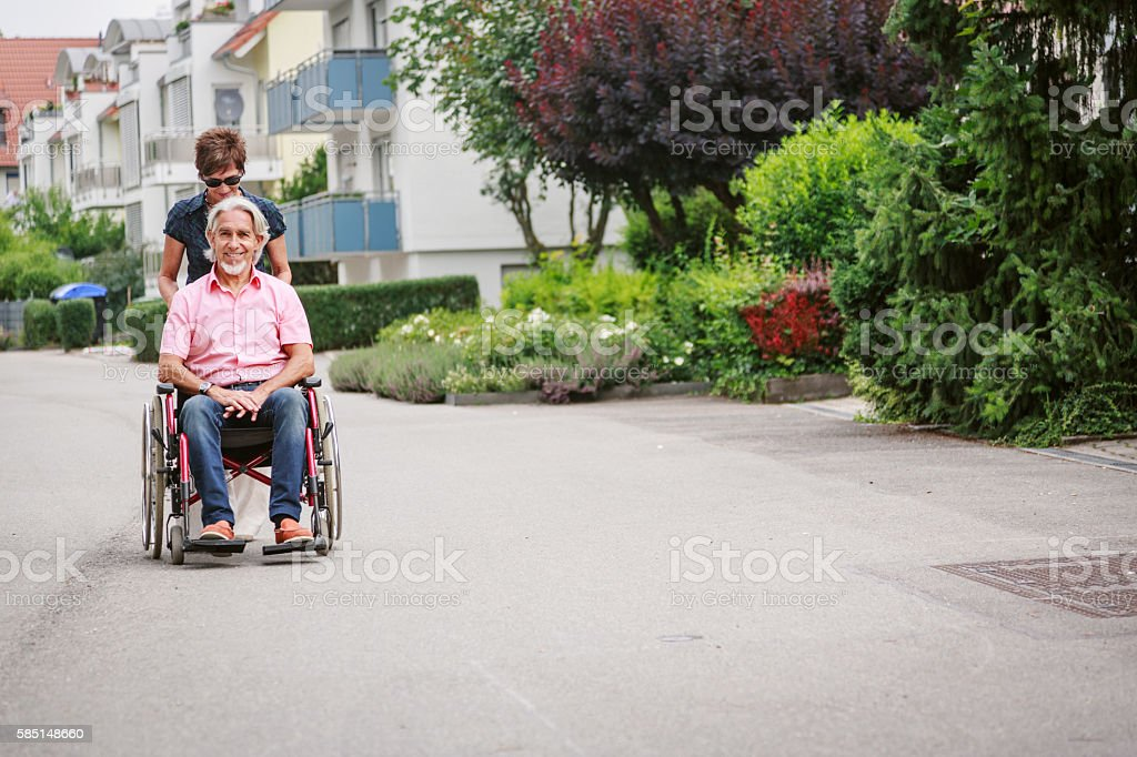Senior couple in wheelchair, enjoying a day in the city stock photo