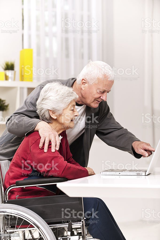 Senior Couple In Wheelchair Using laptop stock photo