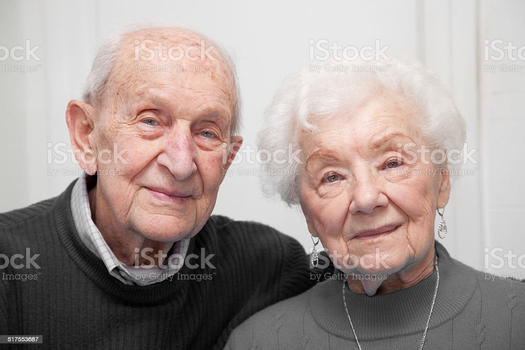 Senior couple indoors smiling monochromatic color. stock photo