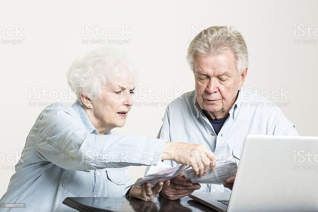 Senior couple is looking at bills concerned royalty-free stock photo