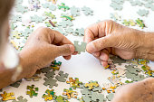 Senior Couple is Playing Puzzle.