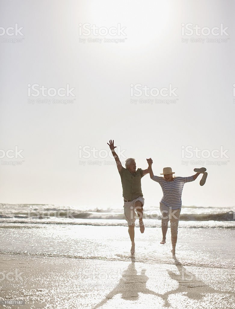 Senior couple jumping on beach royalty-free stock photo