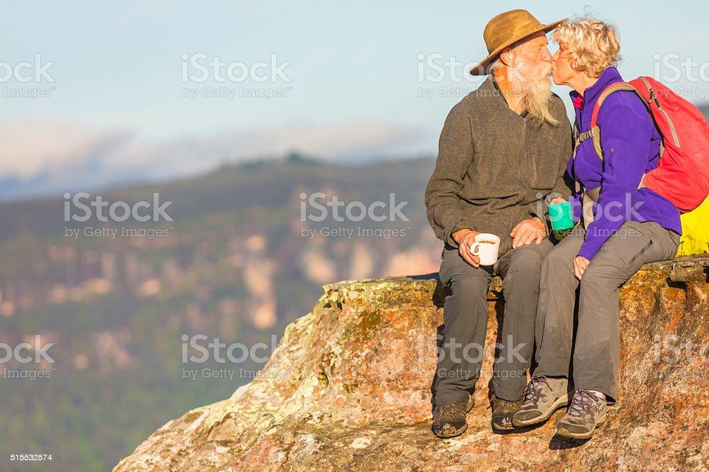 Senior Couple Kissing While Taking a Break from Bushwalking stock photo
