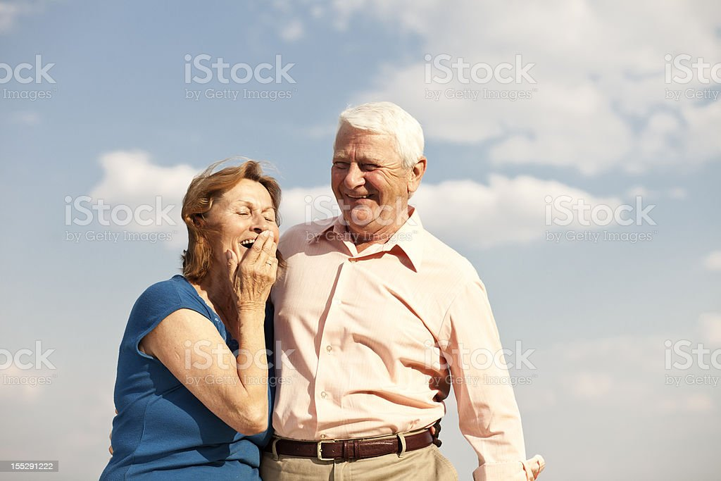 Senior couple laughing with their arms around each other royalty-free stock photo