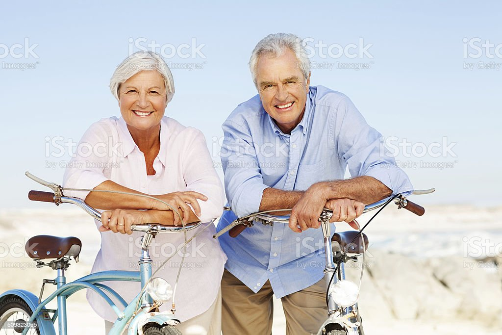 Senior Couple Leaning On Bicycle's Handlebars At Beach royalty-free stock photo