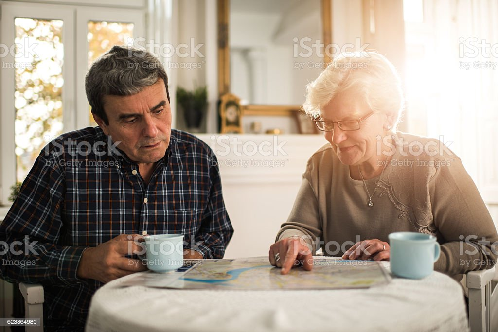 Senior couple looking at a map during coffee time. stock photo