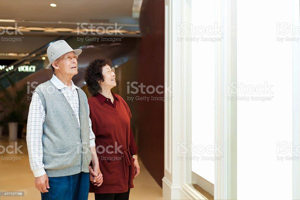 Senior couple looking at blank frame stock photo